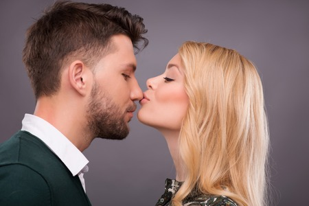 Half-length portrait of beautiful happy blonde with closed eyes wearing patterned shirt standing aside kissing his handsome boyfriend in the nose. Isolated on dark background photo