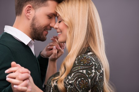 Half-length portrait of lovely happy smiling couple standing with closed eyes facing each other dancing enjoying the moment they are together. Isolated on dark background