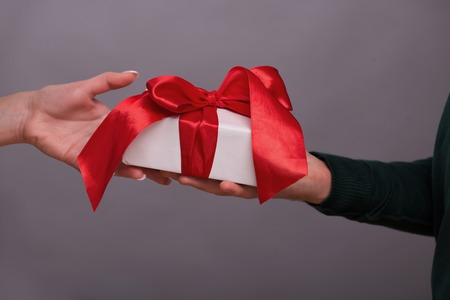 A great present cording with the red band in the hands of two people in love. Isolated on grey background photo