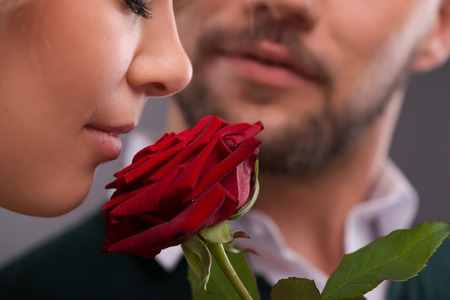 Selective focus on the beautiful young fair-haired woman smelling red rose present from her boyfriend standing on background photo