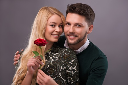 Half-length portrait of young handsome man wearing green sweater and white shirt hugging and presenting his lovely fair-haired smiling girlfriend wonderful red rose. Isolated on grey background photo