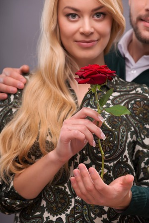 Selective focus on the great red rose in the hands of happy lovely couple standing on background photo
