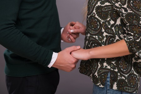 Half-length portrait of young lovely couple standing aside together holding hands. Isolated on dark background photo