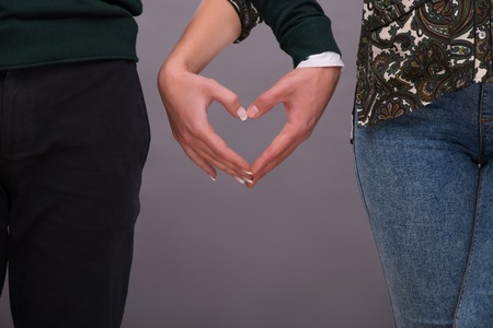 Half-length portrait of young lovely couple standing together holding hands making a form of little heart. Isolated on dark background photo