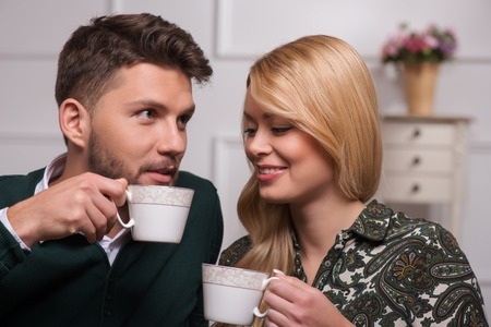 Selective focus on the lovely couple sitting together talking about their new family life drinking tea laughing looking at each other photo