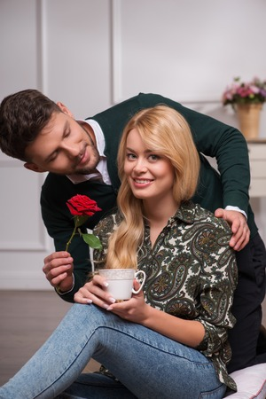 Selective focus on the handsome young man wearing green sweater looking at his girlfriend presenting her a beautiful red rose photo