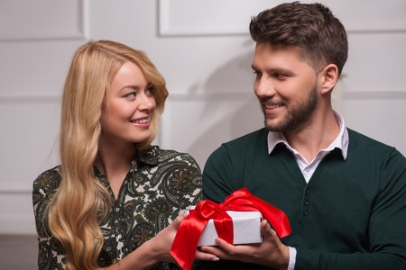 Selective focus on the handsome happily surprised young man wearing green sweater looking at his beautiful fair-haired girlfriend giving him wonderful present photo