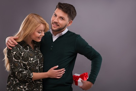 Half-length portrait of young handsome man wearing green sweater and white shirt hiding a beautiful present from his lovely fair-haired smiling girlfriend. Isolated on grey background photo