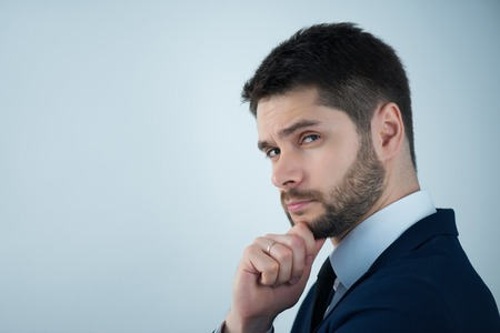 Half-length portrait of handsome young bearded thoughtful man wearing white shirt tie and blue jacket standing aside wanted to remember something. Isolated on white background Stock Photo