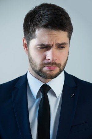 grieved: Half-length portrait of handsome young bearded grieved man wearing white shirt tie and blue jacket thinking about something. Isolated on white background Stock Photo