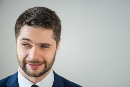 suspiciously: Half-length portrait of handsome young bearded man wearing white shirt tie and blue jacket looking suspiciously at someone. Isolated on white background Stock Photo