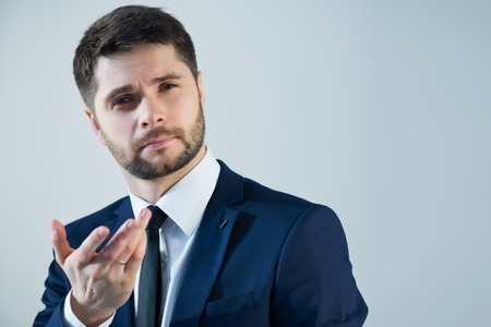 Half-length portrait of handsome young bearded thoughtful man wearing white shirt tie and blue jacket. Isolated on white background
