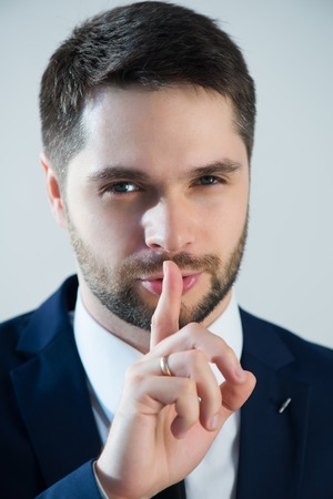 Half-length portrait of handsome young bearded man wearing white shirt tie and blue jacket wanted we keep calm. Isolated on white background Stock Photo