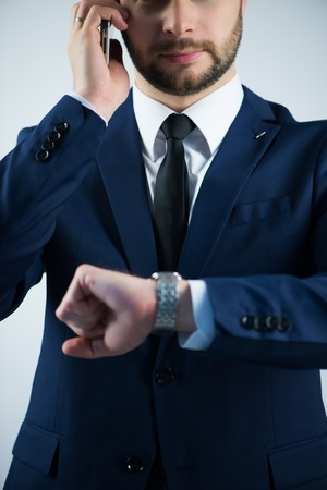 Half-length portrait of handsome young bearded busy man wearing white shirt tie and blue jacket calling his subordinate and looking at his watch. Isolated on white background Stock Photo