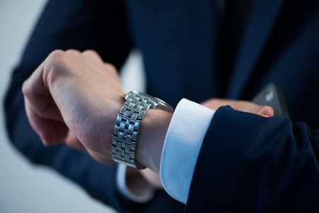 Selective focus on the watch on the hand of busy man wearing white shirt tie and blue jacket
