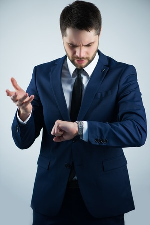 Half-length portrait of handsome young bearded busy man wearing white shirt tie and blue jacket looking at his watch noticed that he is late. Isolated on white background Stock Photo