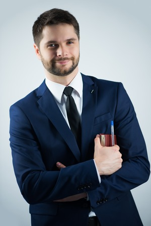 Half-length portrait of handsome young bearded smiling man wearing white shirt tie and blue jacket holding his dairy. Isolated on white background photo