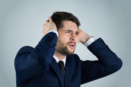 hombre pobre: Retrato de medio cuerpo de hombre pobre joven guapo con camisa blanca corbata y traje azul que sufre de dolor de cabeza. Aislado en el fondo blanco