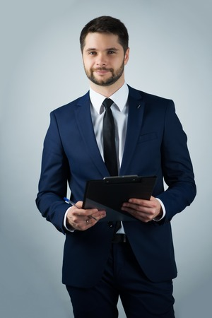 Half-length portrait of handsome young bearded smiling man wearing white shirt tie and blue suit holding the black folder looking at us. Isolated on white background