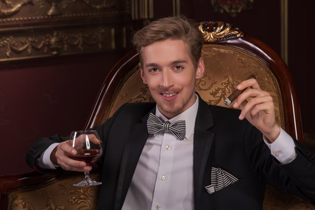 Half-length portrait of handsome young smiling fair-haired man wearing classic costume sitting on the expensive class armchair holding a glass of brandy and smoking his favorite Cuban cigar enjoying his life Stock Photo