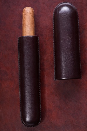 Wonderful Cuban cigar lying in the leather cigar case on the wooden table photo