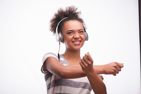 Half-length portrait of young smiling African girl wearing striped T-shirt standing holding mp3 player in her hand and great earphones on the head listening to the music and dancing. Isolated on white background photo