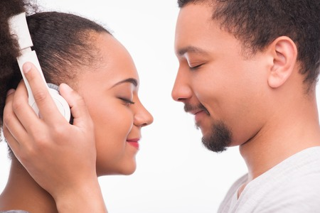 Half-length portrait of handsome man wearing white T-shirt standing aside with closed eyes putting on the earphones on his girlfriend standing opposite him. Isolated on white background photo