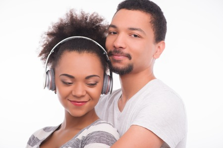 Half-length portrait of young smiling African woman keeping earphones on her head standing with closed eyes in the arms of her boyfriend satisfied with her life. Isolated on white background photo
