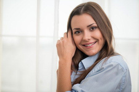 wellness sleepy: Half-length portrait of dark-haired beautiful smiling girl wearing blue shirt standing aside touching her neck looking at us thinking about wonderful last date