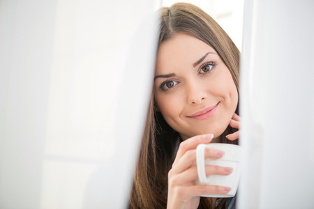 wellness sleepy: Selective focus on the dark-haired beautiful smiling girl waking up in the morning standing near the window looking out of the white curtains holding a cup of hot delicious coffee Stock Photo