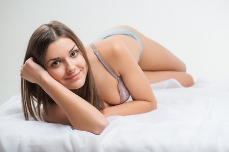 wellness sleepy: Selective focus on the beautiful dark-haired smiling girl wearing sexy bra lying in the bed looking at us thinking about her future date