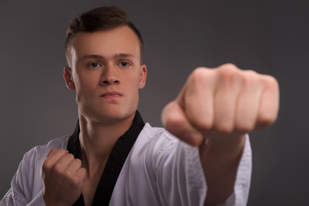 kata: Selective focus on the young handsome fair-haired karate enthusiast wearing white kimono coaching himself before the important fight Stock Photo