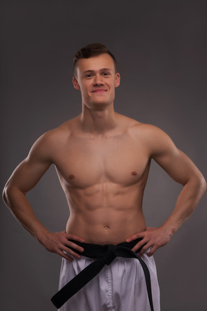bare chested: Half-length portrait of young handsome fair-haired bare-chested karate enthusiast standing and smiling to us. Isolated on the dark background