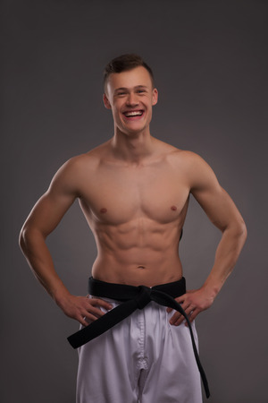 barechested: Half-length portrait of young handsome fair-haired bare-chested karate enthusiast standing and smiling to us. Isolated on the dark background