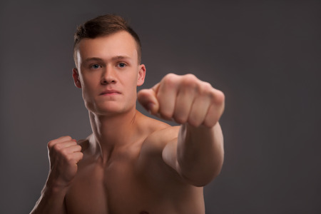 bare chested: Selective focus on the young handsome fair-haired bare-chested karate enthusiast coaching himself before the important fight