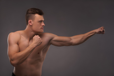 bare chested: Half-length portrait of young handsome fair-haired bare-chested karate enthusiast standing aside training himself before the important fight. Isolated on the dark background Stock Photo