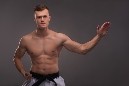 bare chested: Half-length portrait of young handsome fair-haired bare-chested karate enthusiast standing showing us one of his famous motions. Isolated on the dark background