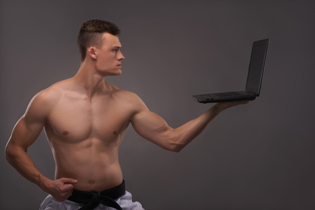 bare chested: Half-length portrait of young handsome fair-haired bare-chested karate enthusiast standing aside with the lap top. Isolated on the dark background