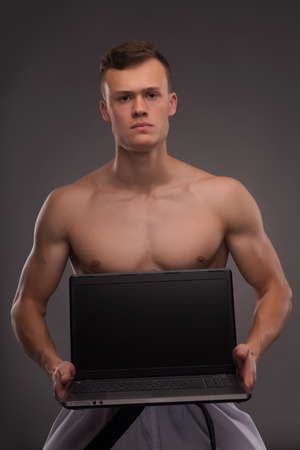 bare chested: Half-length portrait of young handsome fair-haired bare-chested karate enthusiast standing showing us his lap top. Isolated on the dark background