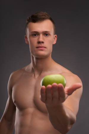 bare chested: Selective focus on the young handsome fair-haired bare-chested karate enthusiast holding on his palm delicious green apple on background Stock Photo