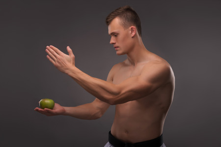 barechested: Half-length portrait of young handsome fair-haired bare-chested karate enthusiast standing aside training his attention focusing on the apple. Isolated on the dark background Stock Photo