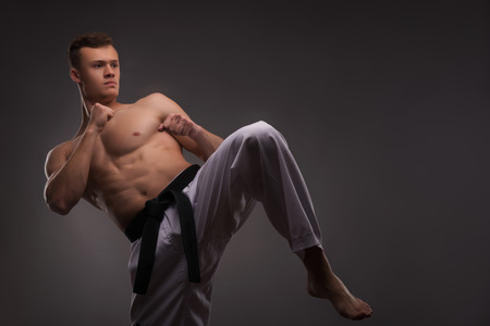 bare chested: Half-length portrait of young handsome fair-haired bare-chested karate enthusiast standing training his strike before the important competition. Isolated on the dark background