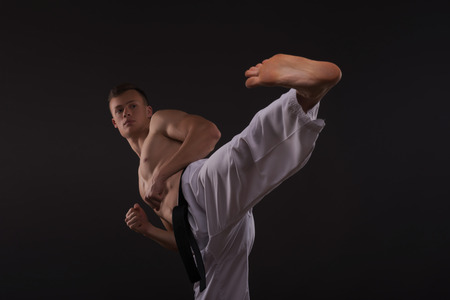 barechested: Half-length portrait of young handsome fair-haired bare-chested karate enthusiast standing training his strike before the important competition. Isolated on the dark background
