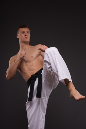 bare chested: Full-length portrait of young handsome fair-haired bare-chested karate enthusiast standing training his strike before the important competition. Isolated on the dark background