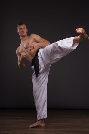 barechested: Full-length portrait of young handsome fair-haired bare-chested karate enthusiast standing training his strike before the important competition. Isolated on the dark background