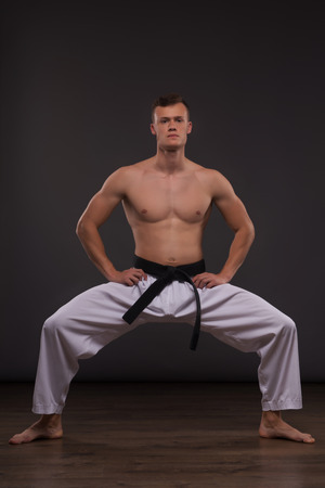 bare chested: Full-length portrait of young handsome fair-haired bare-chested karate enthusiast standing trying to concentrate. Isolated on the dark background