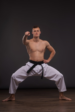 barechested: Full-length portrait of young handsome fair-haired bare-chested karate enthusiast standing trying to concentrate. Isolated on the dark background