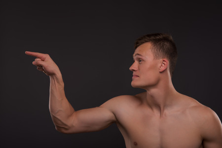 bare chested: Half-length portrait of young handsome fair-haired bare-chested karate enthusiast standing aside asking someone to take his challenge. Isolated on the dark background