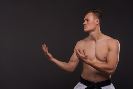 barechested: Half-length portrait of young handsome fair-haired bare-chested karate enthusiast standing aside asking someone to take his challenge. Isolated on the dark background