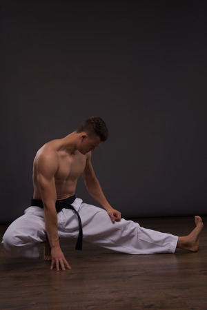 bare chested: Full-length portrait of young handsome fair-haired bare-chested karate enthusiast stretching. Isolated on the dark background Stock Photo